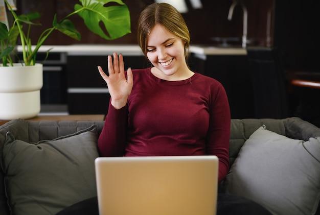 自宅でコンピューターを使用して美しい若い女性の笑顔。高品質の写真