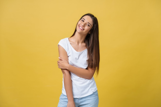 Smiling beautiful young woman in white shirt looking to camera. three quarter length studio shot on yellow background.