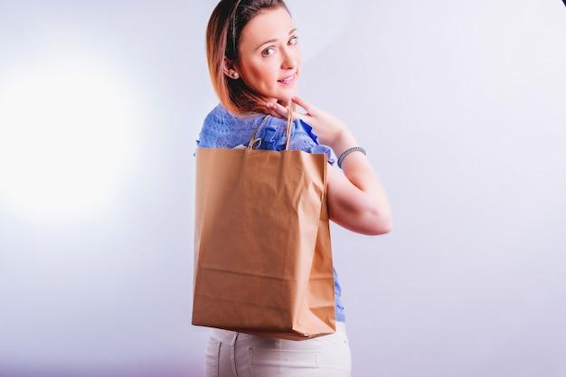Улыбается красивая молодая женщина с бумажным пакетом за спиной. экологичная концепция покупок. без пластика