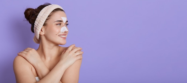 Smiling beautiful young woman with clean perfect skin looking dreamily aside and touching her bare shoulder, doing beauty procedures