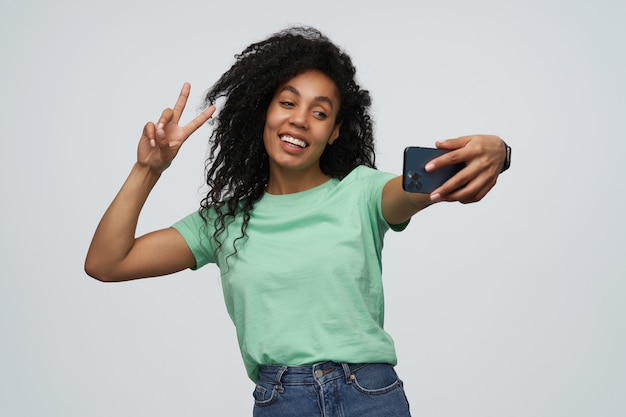 Bella giovane donna sorridente con capelli ricci lunghi in maglietta della menta che prende la foto del selfie usando il telefono cellulare e che mostra il segno di pace isolato sopra la parete grigia