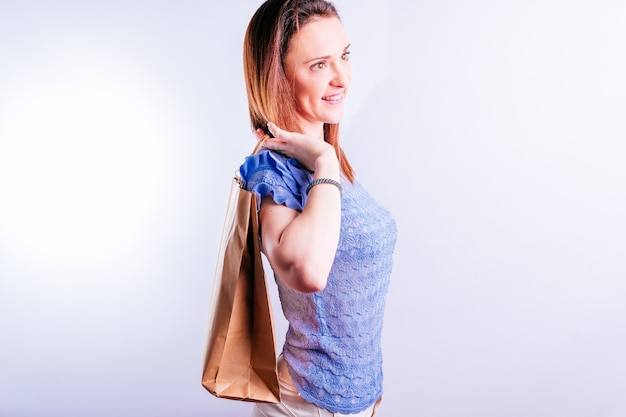 Smiling beautiful young woman with a paper bag behind her back. sustainable shopping concept. plastic free