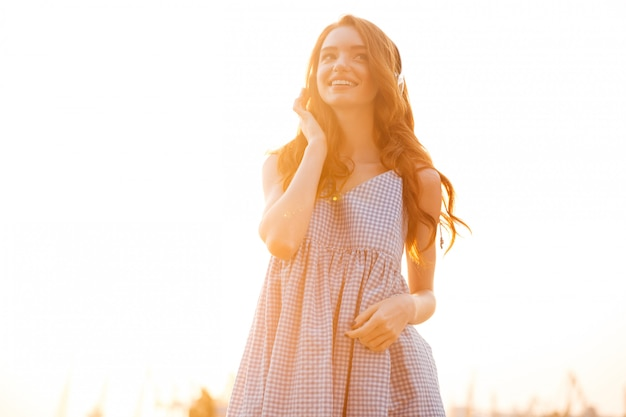 Smiling beauty ginger woman in dress listening music
