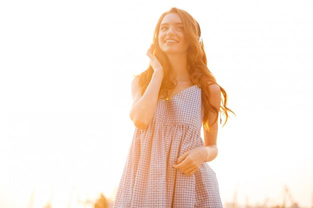 Улыбающаяся красавица рыжая женщина в платье слушает музыку