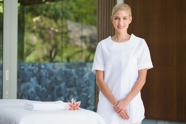 Smiling beauty therapist standing beside massage towel