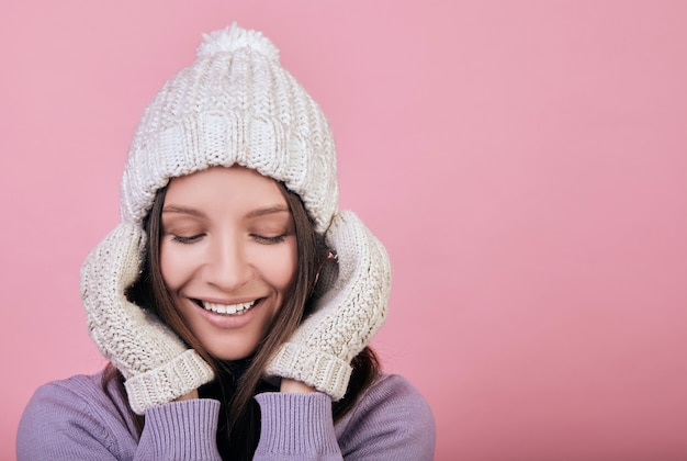 Smiling beauty woman with closed eyes in a winter white knitted hat and white mittens