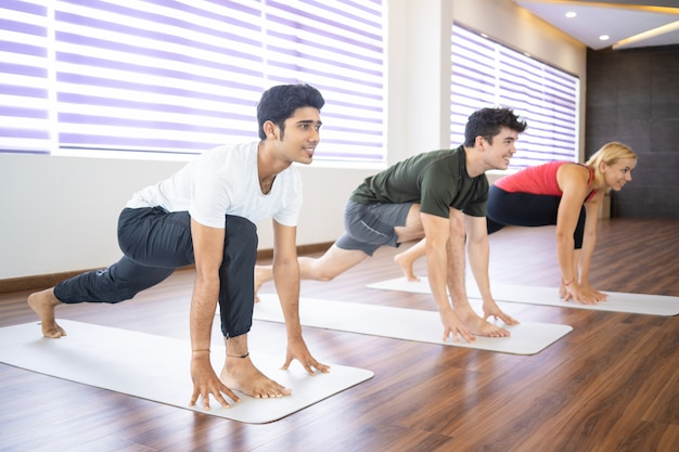 Smiling beginners practicing yoga at class