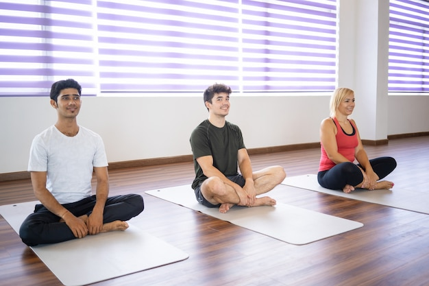 Smiling beginners sitting on mats at yoga class