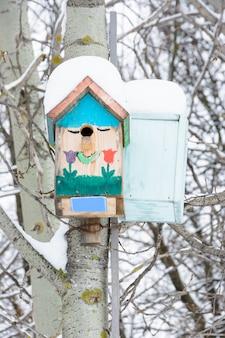 Улыбающиеся скворечники. скворечник в виде забавной мордашки на дереве. деревянный скворечник ручной работы, покрытый снегом. зимний пейзаж с деревьями, покрытыми снегом и копией пространства.