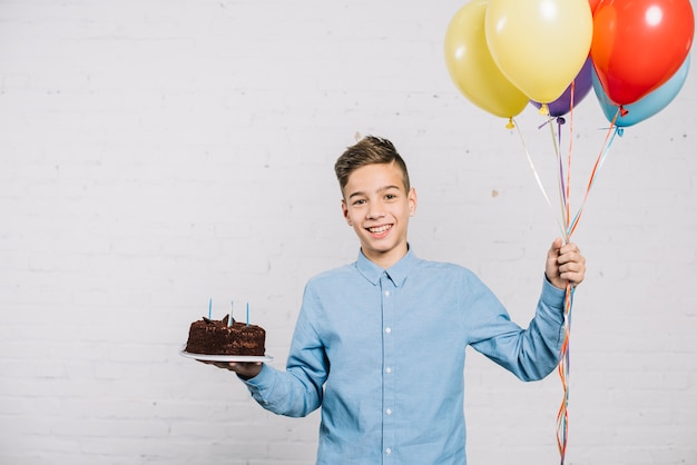 Smiling birthday boy holding balloons and chocolate cake standing against wall