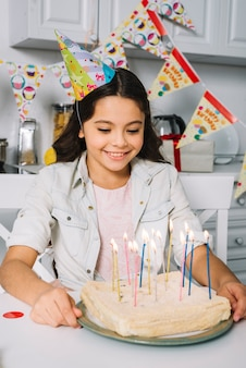 Smiling birthday girl wearing party hat on head looking at cake decorated with colorful candles
