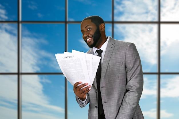 Улыбающийся черный бизнесмен держит контракты.