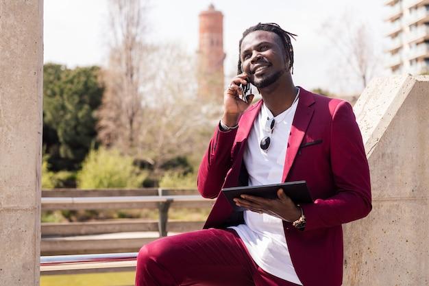 태블릿을 사용하고 도시에서 야외에서 스마트 폰으로 이야기하는 웃는 흑인 사업가