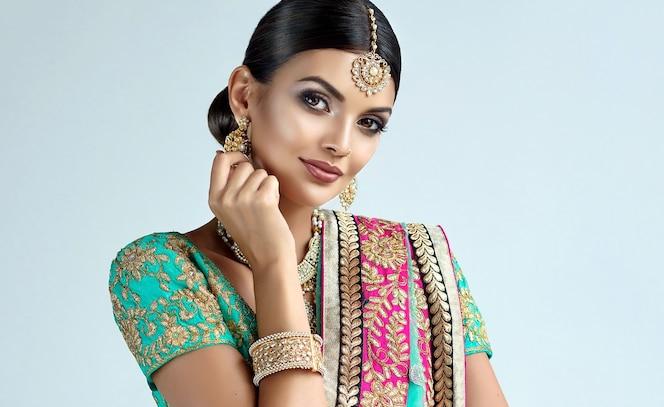 화려한 화장을 하고 머리 티카가 달린 인도 보석 세트를 입은 웃고 있는 검은 눈동자의 여성