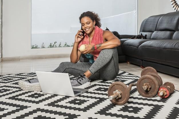 Улыбающаяся черная спортсменка сидит на полу с яблоком и разговаривает по смартфону во время перерыва во время тренировки дома