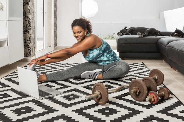 Smiling black female athlete stretching legs and watching video tutorial on laptop while warming up muscles during training at home