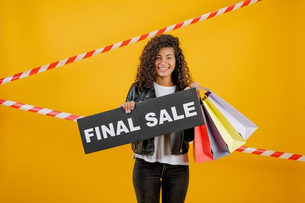 Smiling black girl with final sale sign and colorful shopping bags isolated over yellow with signal tape