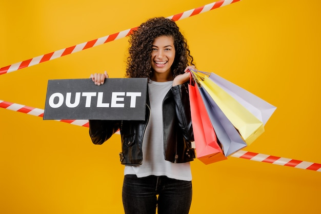 Smiling black girl with outlet sign and colorful shopping bags isolated over yellow with signal tape
