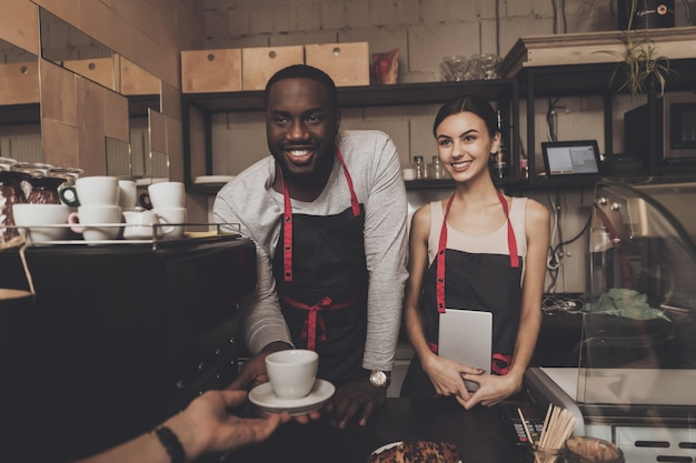 Smiling black guy in apron gives cup of cooked coffee to visitor in cafe. confectionery. barista.