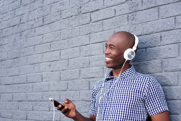 Smiling black  guy with headphones and mobile phone