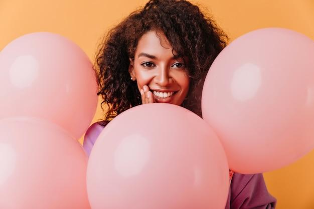 Sorridente bella donna nera con palloncini. ragazza di compleanno isolata sull'arancio.