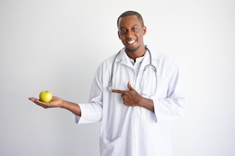 Smiling black male doctor holding and pointing at apple.