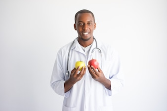 Smiling black male doctor holding yellow and red apple.