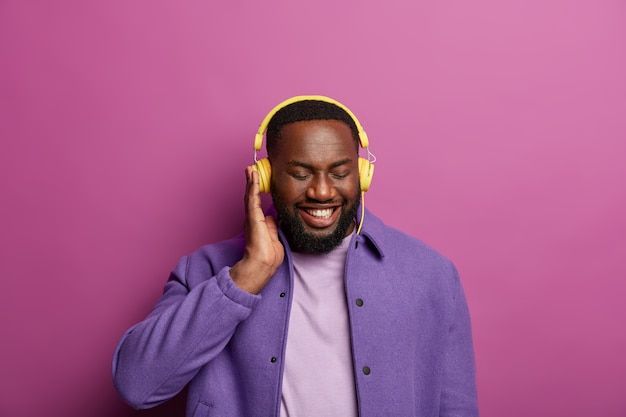 Smiling black man enjoys good sound in headphones, made new playlist, listens favourite music during spare time, dressed in purple jacket, shows white teeth. people