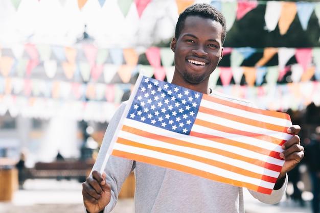 Uomo di colore sorridente che tiene bandiera americana e che guarda l'obbiettivo