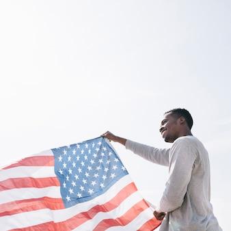 Улыбающийся черный человек держит развевающийся американский флаг на солнце