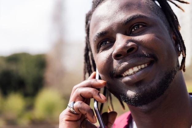 屋外でスマートフォンで話している黒人男性の笑顔