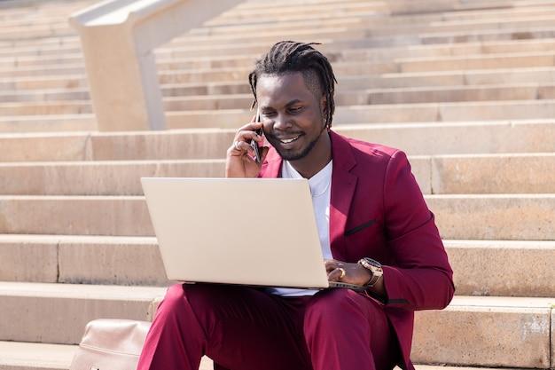 웃고 있는 흑인 남성은 도시 계단에 앉아 컴퓨터 노트북과 전화를 가지고 일한다
