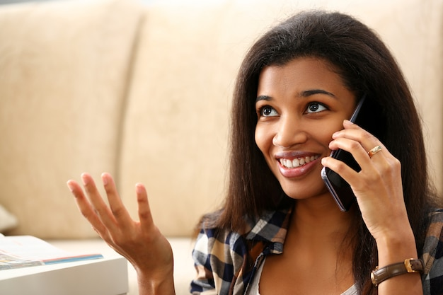 Smiling black woman hold in hand mobile phone at home