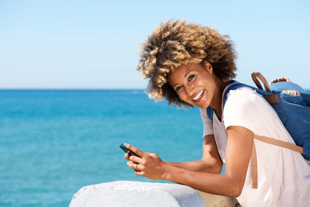 Smiling black woman standing at seaside with smart phone