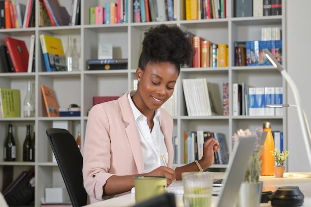 Улыбающаяся темнокожая женщина делает заметки в записной книжке в офисе