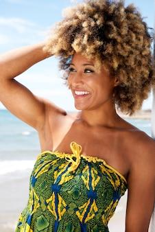 Улыбается черная женщина с вьющимися волосами, стоя на пляже
