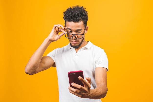Smiling black young man in glasses holding phone and using mobile applications