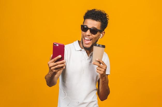 Улыбающийся черный молодой человек в очках держит телефон, изолированный на желтом