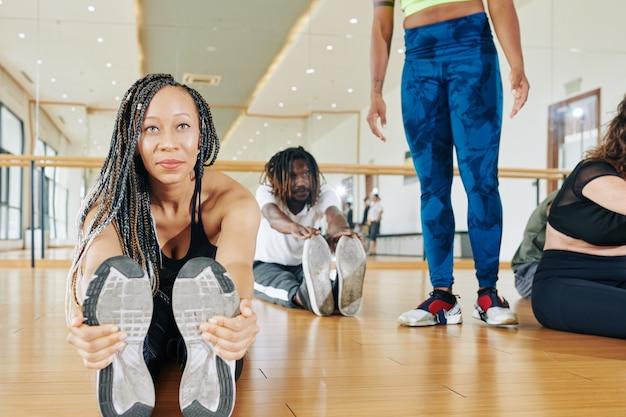 床に座って、つま先に触れて前方に伸びるドレッドヘアを持つ黒人の若い女性の笑顔