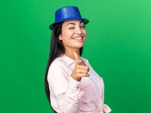 あなたにジェスチャーを示すパーティーハットを身に着けている笑顔のまばたき若い美しい少女