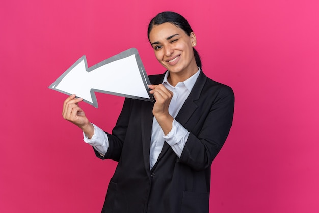 笑顔のまばたき若い美しい女性が方向マークを保持している黒いブレザーを着て