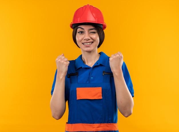 노란 벽에 격리된 예 제스처를 보여주는 제복을 입은 웃는 젊은 건축업자 여성