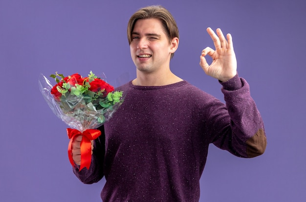 Smiling blinked young guy on valentines day holding bouquet showing okay gesture isolated on blue background