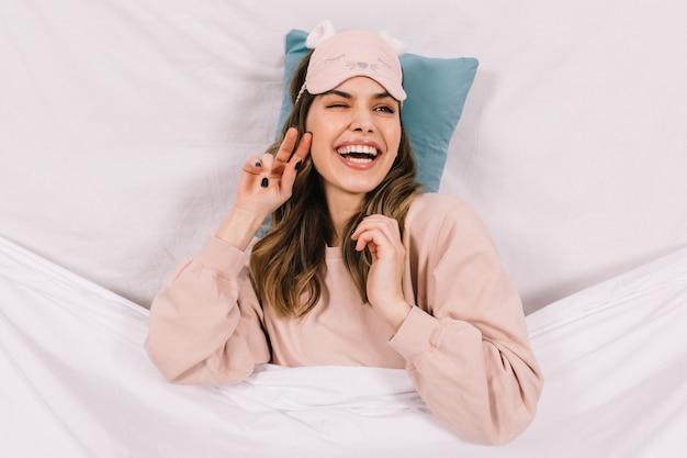 침대에 누워있는 파자마에 웃는 행복한 여자