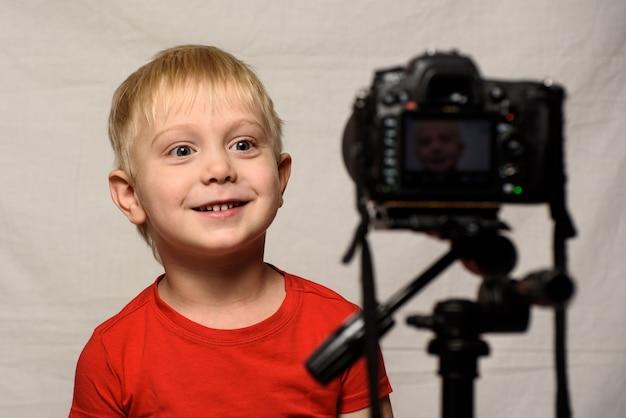 Усмехаясь белокурый мальчик перед объективом фотоаппарата. маленький видео блоггер. домашняя студия
