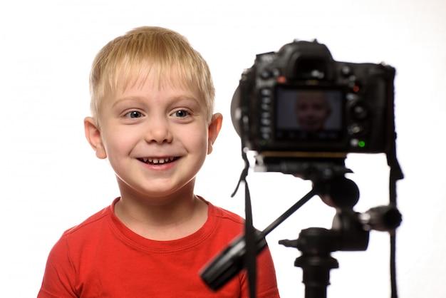 カメラのレンズの前で笑顔の金髪の少年。小さなビデオブロガー。
