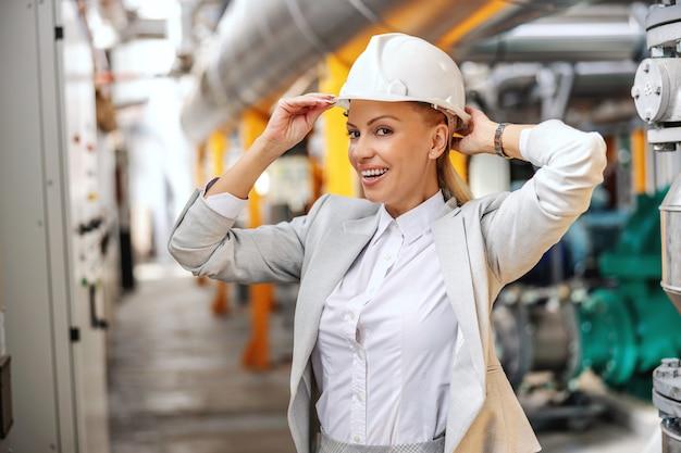 頭に保護ヘルメットをかぶって、発電所を歩き回る準備をしているフォーマルな服装で金髪の実業家を笑顔。