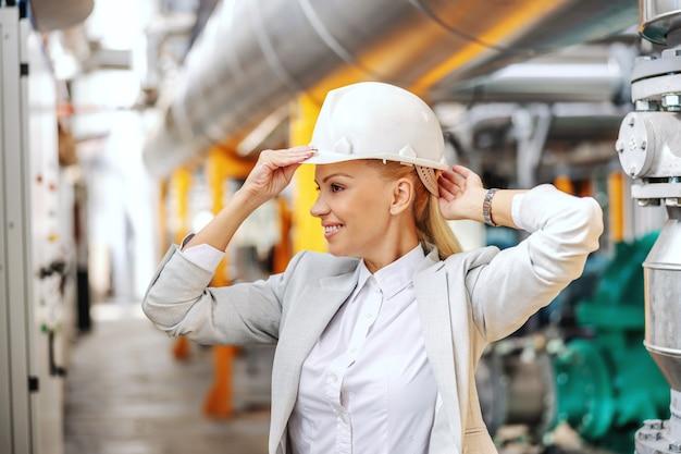 頭に保護ヘルメットを置き、発電所を歩き回る準備をしてフォーマルな服装で金髪の実業家を笑顔