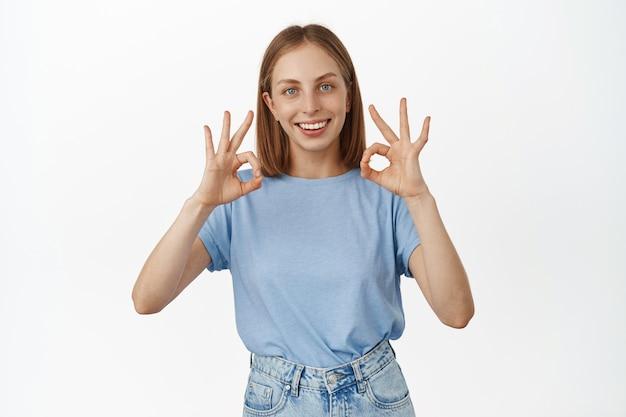 Sorridente donna caucasica bionda mostra segni ok ok, approva qualcosa di interessante, loda un ottimo lavoro, consiglia il prodotto, sta in piedi sul muro bianco