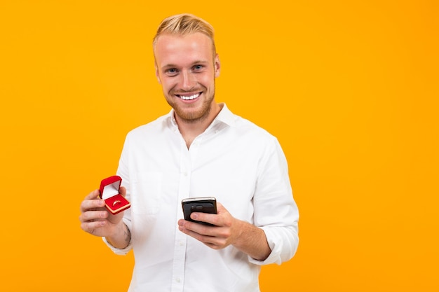 Smiling blond european man makes an offer holding a ring in a box and a phone on a yellow background.